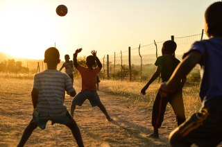 Young boys play football in the dying light. Swaziland, June 2015.