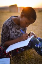 Phindiswe, age 14, does her English homework as the sun sets. Swaziland, June 2015.