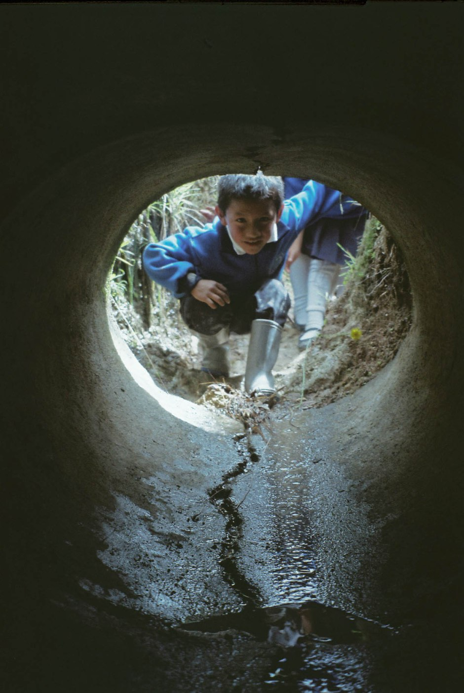 A boy looks through a túnel secreto that runs underneath a road connecting their school to the corn farm on the other side. Chilca Totora, Ecuador.